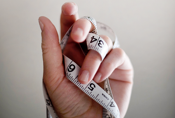 Woman's hand holding a measuring tape