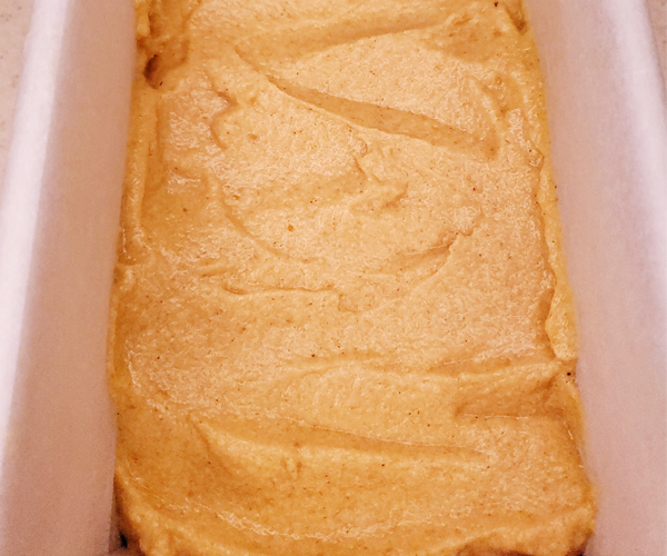 Batter poured into a lined loaf pan