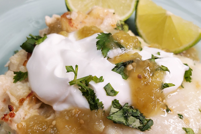 chicken verde bake on a plate with sour cream close up